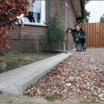 """Fedor Buitenhuis heeft zelf alvast een goot aangelegd langs zijn huis. Een extra lange, want zijn regenpijp zit aan de achterzijde van zijn woning aan de Zanderijweg. Buitenhuis noemt de afkoppeling van regenwater een mooi idee. ,,Waarom water bij de rioolzuivering zuiveren dat al schoon is."""" (foto Cees Baars)"""