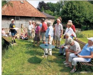 In het zonnetje luisteren deelnemers aan de excursie naar het verhaal van de kopermolen.  (foto: Cees Baars.)
