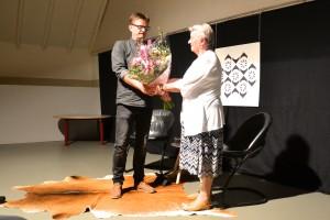 Voorzitter Jeroen Voskuilen overhandigt bloemen aan molenbewoonster Annie van Silfthout bij de opening van de nieuwe Molenplaats.